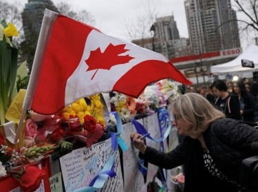 A mourner writes a message on a makeshift memorial a day after a van struck multiple people along a major intersection in north Toronto, Ontario, Canada, April 24, 2018
