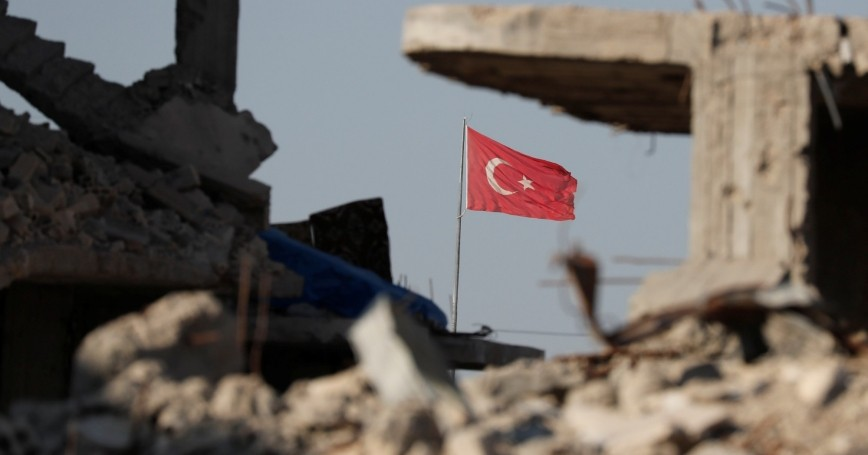 Turkish flag flutters at Turkey's border gate with Syria, overlooking ruins of buildings destroyed during fighting with the Islamic State militants in Kobani, Syria, October 11, 2017
