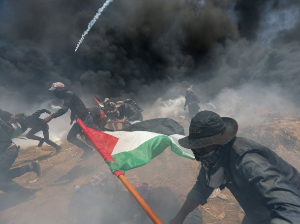 Palestinian demonstrators run for cover from Israeli fire and tear gas during a protest against the U.S. embassy move to Jerusalem and ahead of the 70th anniversary of Nakba, at the Israel-Gaza border in the Gaza Strip, May 14, 2018