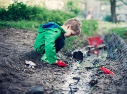 Little boy playing in a dirty drain trench