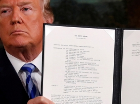 U.S. President Trump holds up a proclamation declaring his intention to withdraw from the JCPOA Iran nuclear agreement after signing it at the White House, May 8, 2018