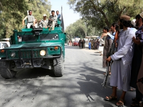 A Taliban (R) stands as Afghan security forces ride on an army vehicle during a celebration of a ceasefire in Nangarhar province, Afghanistan, June 16, 2018