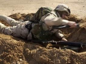 Construction Electrician 3rd Class Justin Vizcarrondo uses an entrenching tool to dig a hasty scrape during field combat training operations, February 9, 2003
