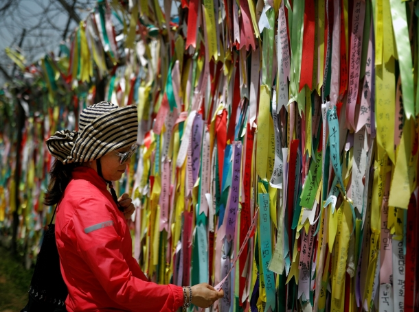 A woman looks at ribbons bearing messages wishing for the unification of two Koreas that decorate a barbed-wire fence near the demilitarized zone separating the two Koreas in Paju, South Korea, May 24, 2018