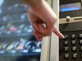 Hand pushing vending machine button