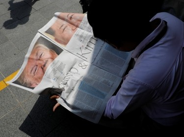 A journalist reads a local newspaper showing an article on the summit between U.S. President Donald Trump and North Korean leader Kim Jong Un near St. Regis hotel in Singapore, June 11, 2018