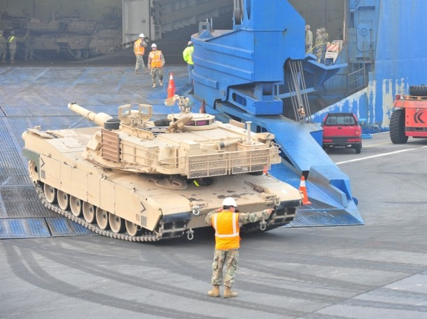 A U.S. Army Soldier guides an M1 Abrams Main Battle Tank from 1st Armored Brigade Combat Team, 1st Cavalry Division, off the ramp of the ARC vessel Endurance May 20 at the Port of Antwerp, Belgium, May 20, 2018