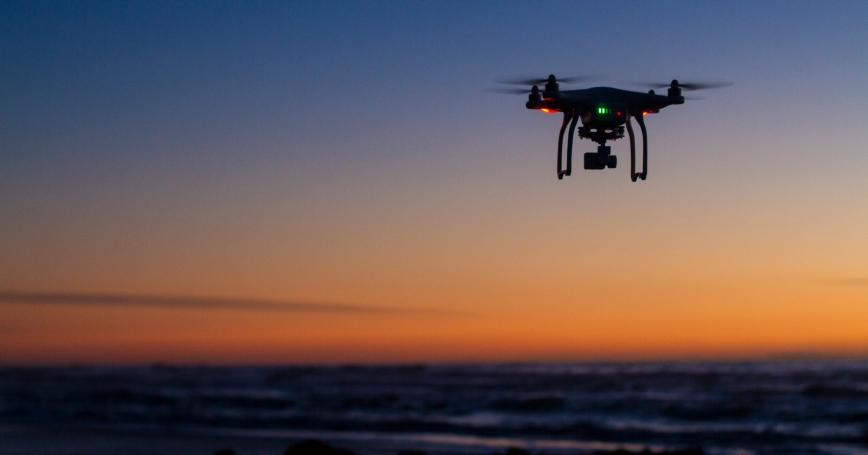 A drone flies over the ocean at dawn