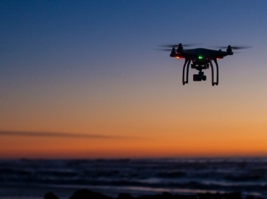 A drone flies over the ocean at dawn