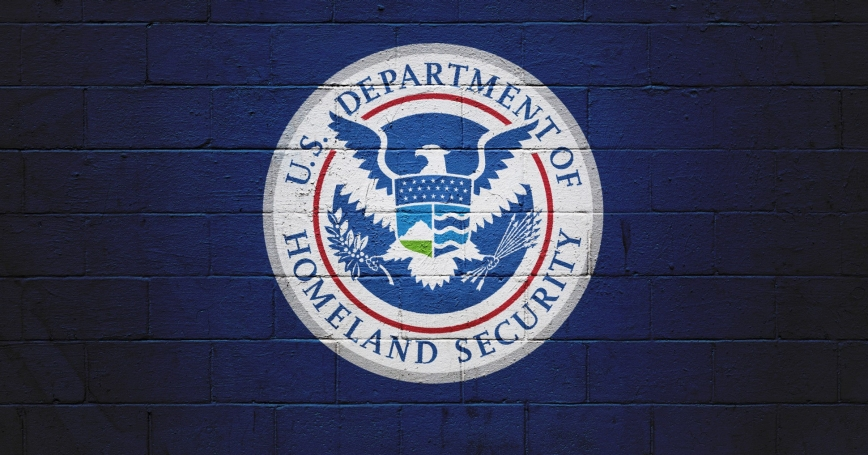 DHS seal painted on brick wall