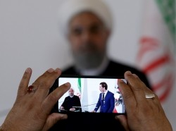 Iran's President Hassan Rouhani and Austria's Chancellor Sebastian Kurz are seen on the mobile phone screen as they attend a news conference at the Chancellery in Vienna, Austria July 4, 201,8