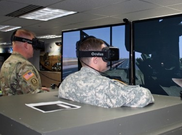 Maj. Mike Stinchfield, left, and Maj. Greg. Pavlichko, demonstrate the virtual capabilities of the Stryker Virtual Collective Trainer concept at the Combined Arms Center - Training Innovation Facility on Fort Leavenworth, Kansas