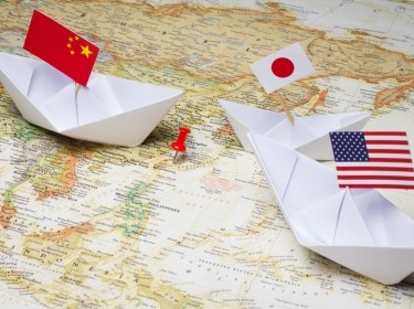 Paper boats with flags of China, Japan, and the United States on a map of East Asia