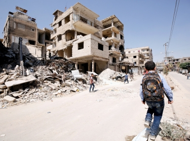 A student walks along a damaged street in the town of Kafr Batna, in eastern Ghouta, Syria, September 5, 2018