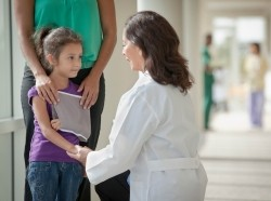 A doctor talks to a girl whose arm is in a sling