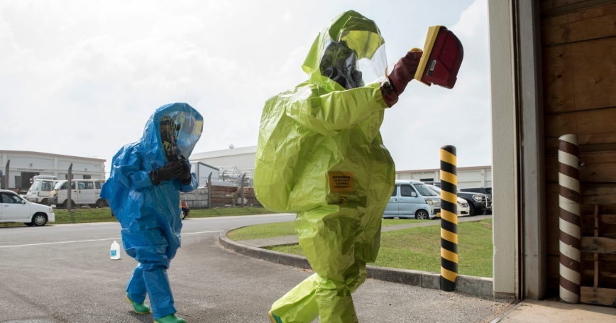 U.S. Air Force Airman Brittany Harris, 18th Civil Engineer Squadron Emergency Management Flight EM operations apprentice, and Senior Airman Isaiah Flemings, 18th Aerospace Medicine Squadron bioenvironmental engineering technician, enter a staged scene of a hazardous materials incident during a training exercise August 3, 2017, at Kadena Air Base, Japan