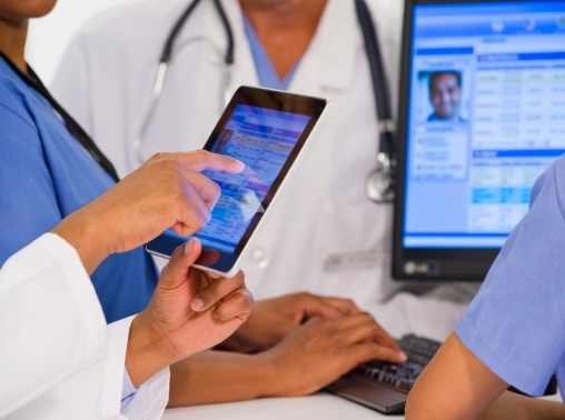 Doctors using a tablet and a computer to view a patient's medical records