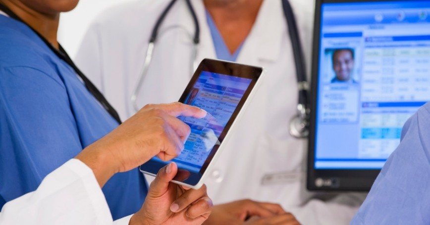 Doctors using a tablet and a desktop computer to view a patient's medical records