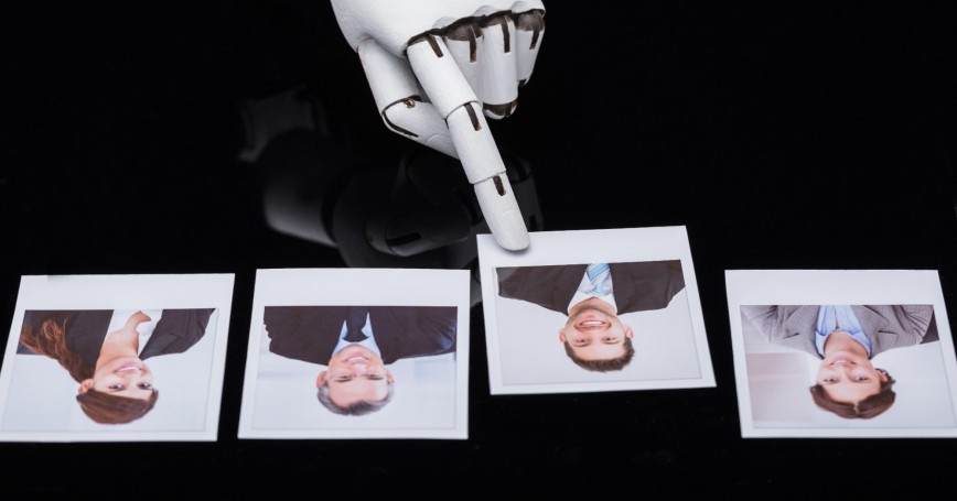 A robot's hand selecting a candidate photograph