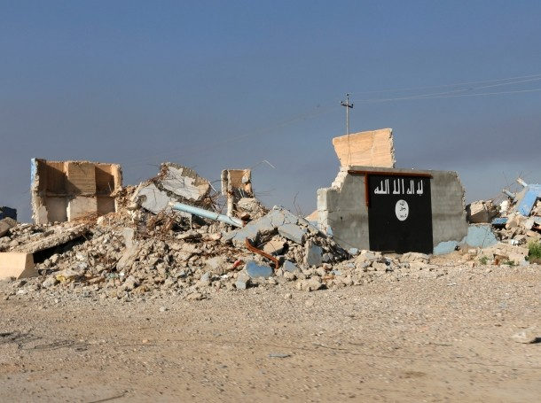 A destroyed building with a wall painted with the black flag commonly used by Islamic State militants, is seen in the town of al-Alam, Iraq, March 10, 2015