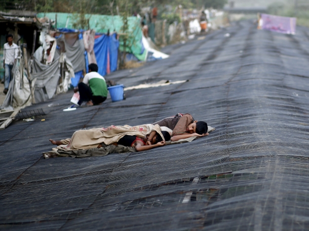 Men sleep on a temporary shade built over a drain next to a slum on a hot summer day in New Delhi, India, May 28, 2015