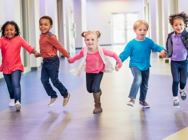 A multi-ethnic group of five preschool children holding hands, running down a hallway in the school building
