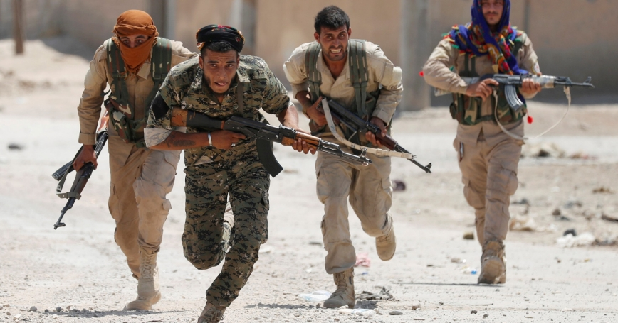 Kurdish fighters from the People's Protection Units (YPG) run across a street in Raqqa, Syria, July 3, 2017