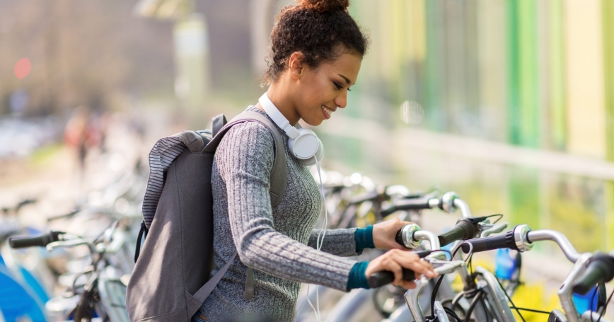 A woman choosing from a row of bicycles