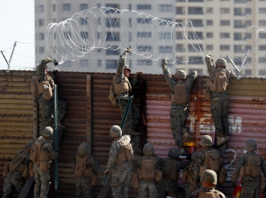 U.S. Marines install concertina wire along the top of the primary border wall at the port of entry next to Tijuana, Meico, in San Ysidro, San Diego, U.S., November 9, 2018