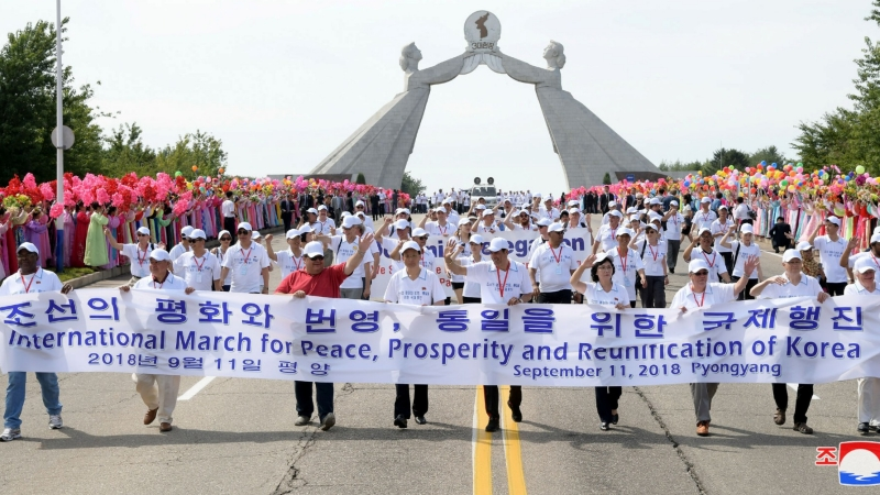 People attend a march for peace, prosperity, and reunification of Korea near the Arch of Reunification in Pyongyang, North Korea, in this undated photo released September 12, 2018 by the Korean Central News Agency