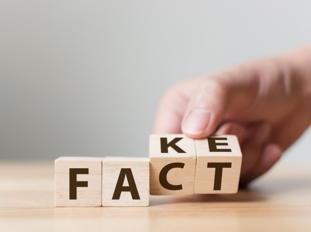 Hand flipping wood cubes to change the word fact to fake