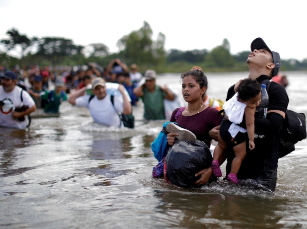 Daniel holds 1-year-old Daniela, both from El Salvador, as a group of migrants from Central America en route to the United States crossed through the Suchiate River into Mexico, November 2, 2018