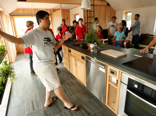 A guide explains the interior of a home designed by students of Middlebury College competing in the Solar Decathlon in Washington, September 26, 2011