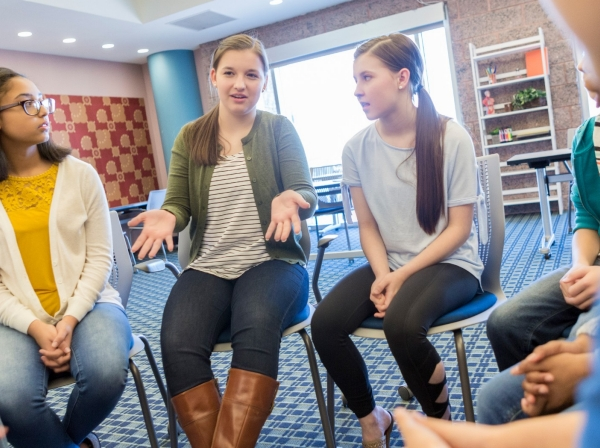 Teenage girl talking at a support group meeting