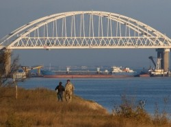 A Russian cargo ship beneath a bridge connecting the Russian mainland with the Crimean Peninsula after three Ukrainian navy vessels were stopped by Russia from entering the Sea of Azov via the Kerch Strait in the Black Sea, Crimea, November 25, 2018