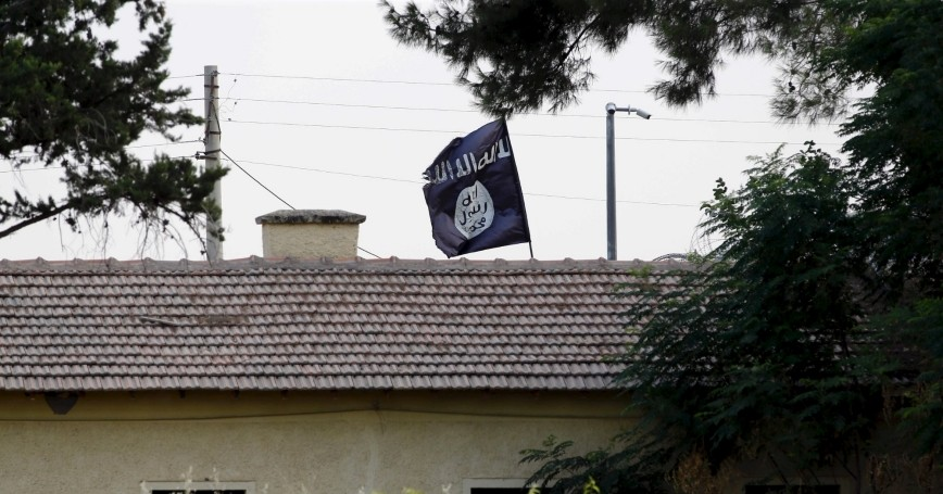 An Islamic State flag flies over the custom office of Syria's Jarablus border gate near the Turkish town of Karkamis, in Gaziantep province, Turkey, August 1, 2015