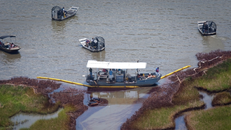Work crews on boats gather to clean marshland impacted by oil from the Deepwater Horizon spill in the Barataria Bay of Louisiana, June 17, 2010.