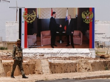 A soldier stands guard near a poster of Syria's President Bashar al Assad and his Russian counterpart Vladimir Putin in Rastan, Syria, June 6, 2018