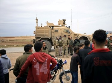 Syrian residents watch as U.S. troops patrol near Turkish border in Hasakah, Syria, November 4, 2018