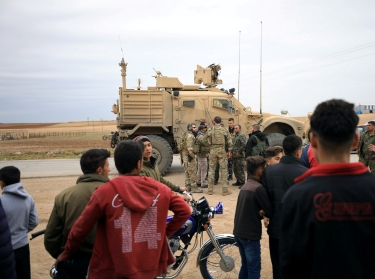 Syrian residents watch as U.S. troops patrol near Turkish border in Hasakah, Syria, November 4, 2018