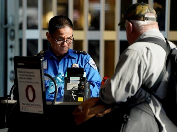 A TSA employee checks the documents of a traveler at Reagan National Airport in Washington, D.C., January 6, 2019