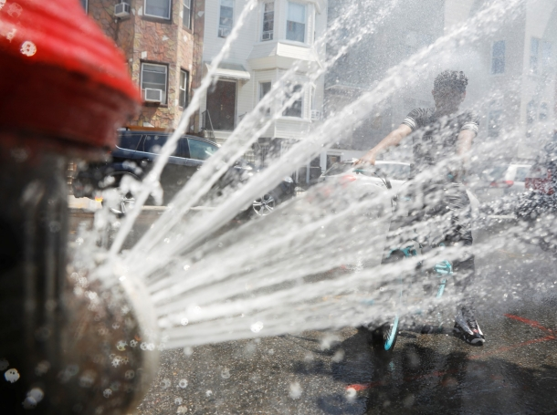 A boy on a bicycle cools off from the extreme heat from an opened fire hydrant in Brooklyn, New York, July 2, 2018