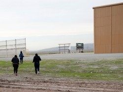 After crossing from Mexico by jumping a border fence, migrants run next to a prototype of the border wall in Otay County, California, December 21, 2018