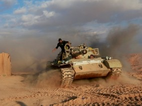 Popular Mobilisation Forces fighters ride in a tank near the Iraqi-Syrian border in al-Qaim, Iraq, November 26, 2018