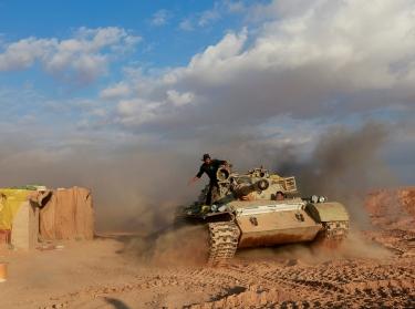 Popular Mobilisation Forces fighters ride in a tank near the Iraqi-Syrian border in al-Qaim, Iraq, November 26, 2018