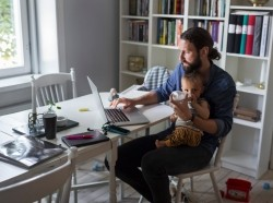 Father working at home with baby