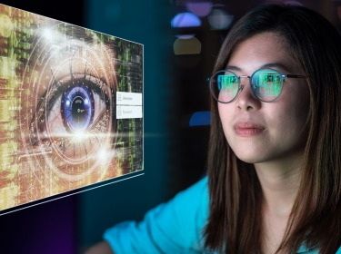 Young Asian woman looking at an eye scanner image, photo by Photographer is my life/Getty Images