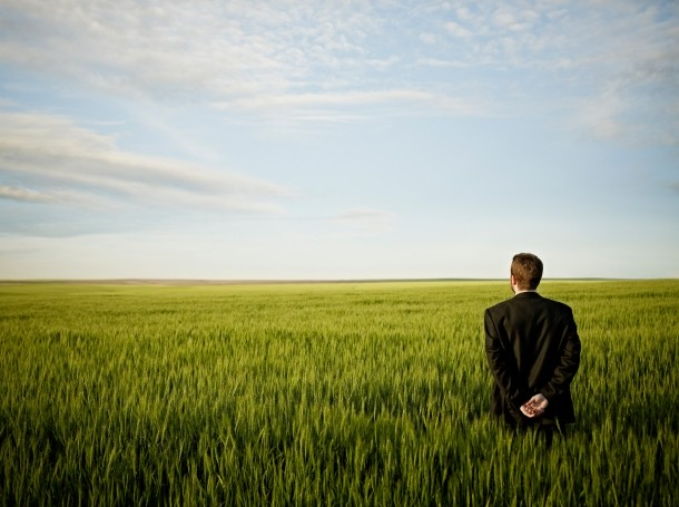 Man in a field looking at the horizon, photo by Thomas Barwick/Getty Images
