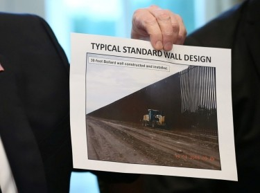 Donald Trump holds up a photo of a border wall design in the Cabinet Room of the White House in Washington, D.C., January 11, 2019, photo by Leah Millis/Reuters