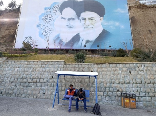 Iranian youths sit under a large picture of Iran's late leader Ayatollah Ruhollah Khomeini (L), and Iran's Supreme Leader Ayatollah Ali Khamenei at a park in Tehran, Iran, January 17, 2016